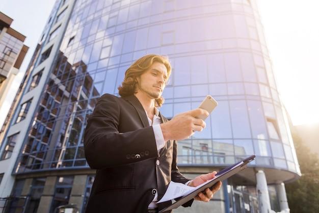 Человек, используя свой телефон в солнечное утро