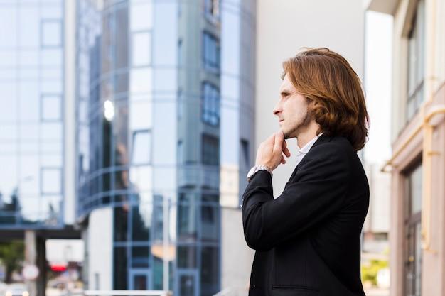 Задумчивый бизнесмен смотрит в сторону