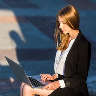 彼女のラップトップを屋外で使う秘書