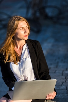 屋外のラップトップを持つ美しい女性