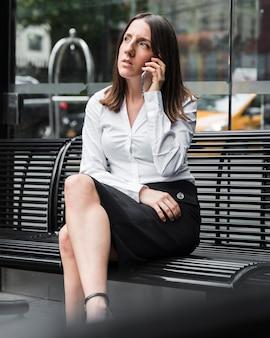 電話でベンチに座っているサイドビュー女性