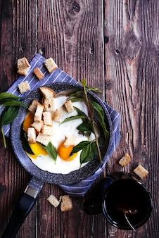 おいしい卵と木製のテーブルでの紅茶の朝食