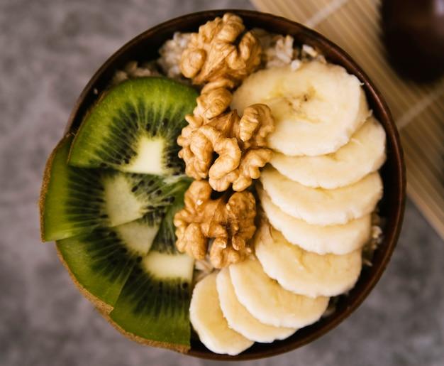 Вид сверху здоровая миска с фруктами и орехами