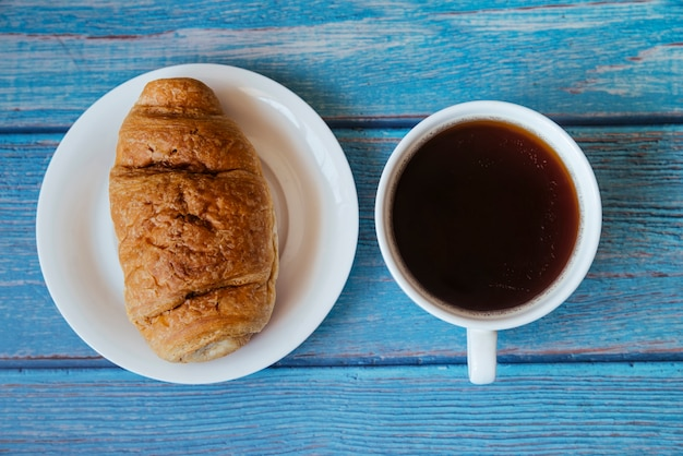トップビュークロワッサンと木製のテーブルの上のコーヒー