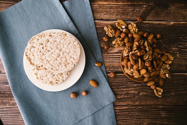 Вид сверху воздушный рис и орехи на деревянном фоне