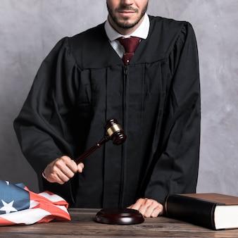 Судья крупным планом с молотком и лепниной