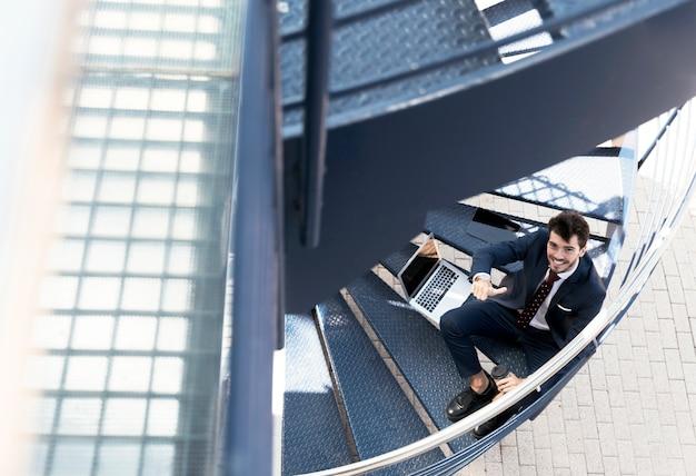 階段の上に座って高角スマイリー弁護士