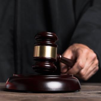 Судья крупного плана в мантии, ударяющей молотком
