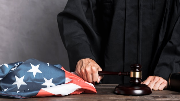 Судья крупным планом с флагом, ударяющим молотком