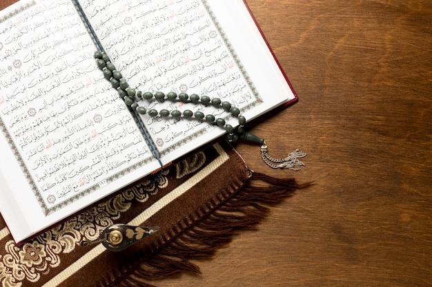 木製の背景にコーランを開く