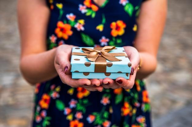 Женщина показывает маленький подарок на праздник