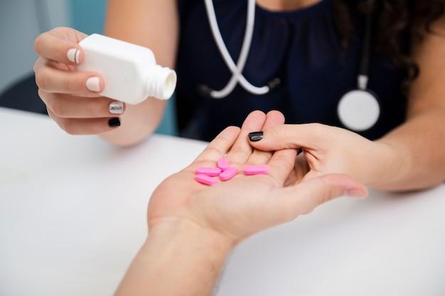 Крупным планом доктор, давая розовые таблетки