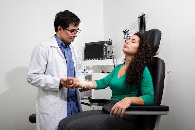 ミディアムショット医師が包帯の腕を調べる
