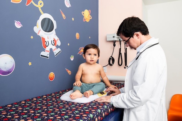 ミディアムショットの医者が赤ちゃんの体重を量る