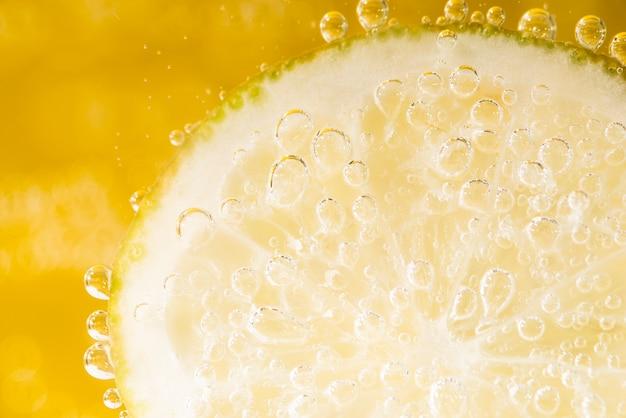 Крупным планом ломтик лимона с пузырьками воды