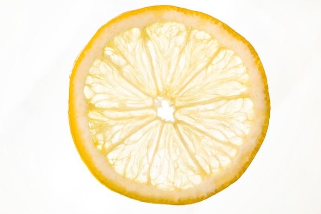 Кислый ломтик лимона на белом фоне