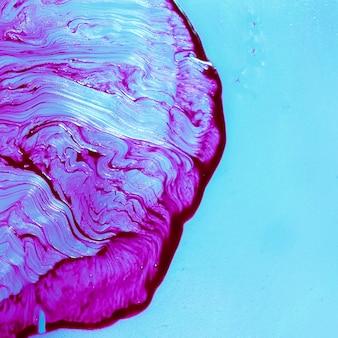 青色の背景に抽象的な滑らかな紫色のテクスチャ