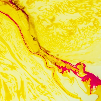Желтый абстрактный фон с косыми линиями липкой жидкости
