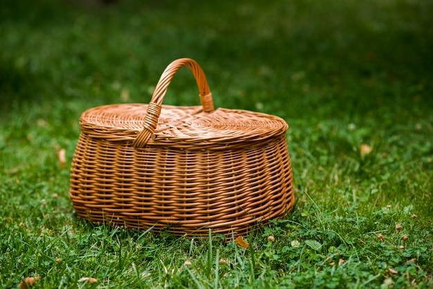 芝生の上の枝編み細工品ピクニックバスケット