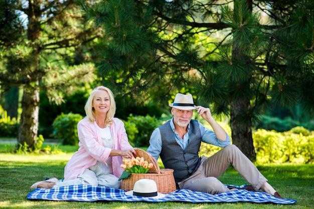 老夫婦のピクニックでカメラにポーズ