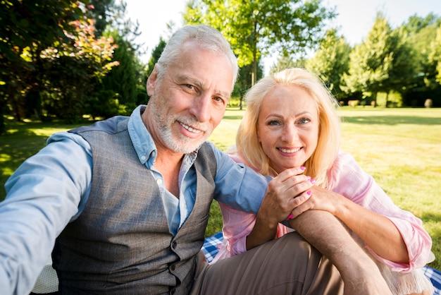 スマイリーカップルが自然にカメラにポーズ