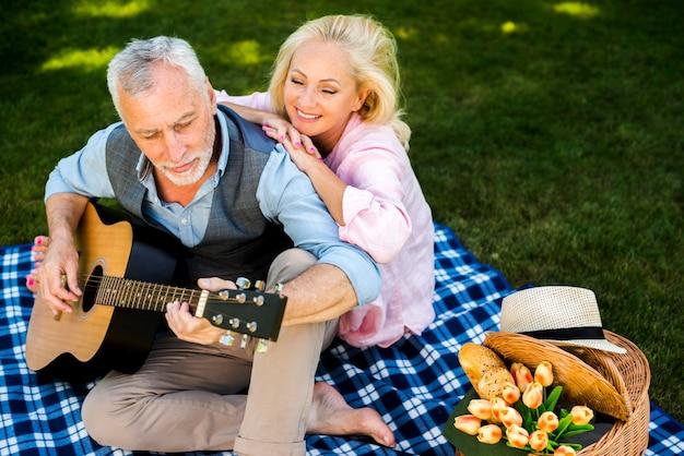 歳の女性が彼女の男のギターの歌を楽しんで