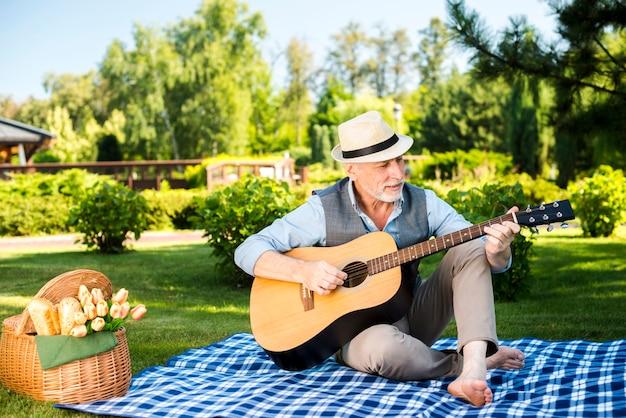 老人男性がギターを弾いて