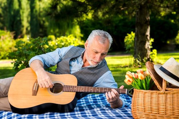 老人男性、ピクニックでギターを弾く