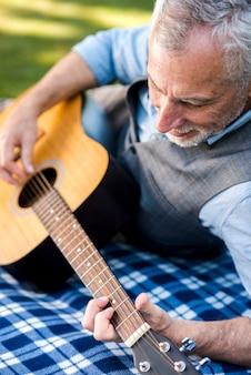 クローズアップの老人男性がギターを弾く