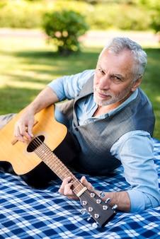 カメラを見ながらギターを弾く男