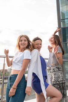 Счастливые девушки танцуют спина к спине