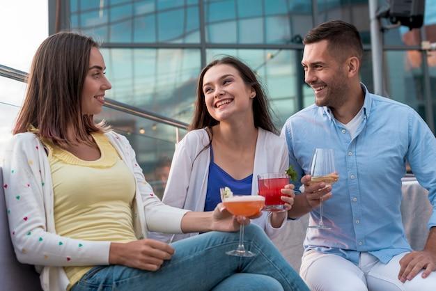 パーティーでドリンクを飲みながら友達と座っている