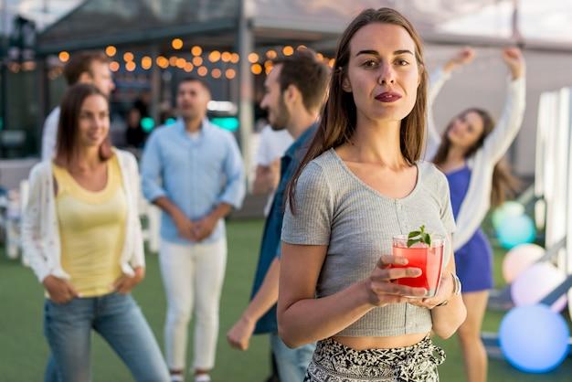 Среднего выстрела женщина позирует с коктейлем