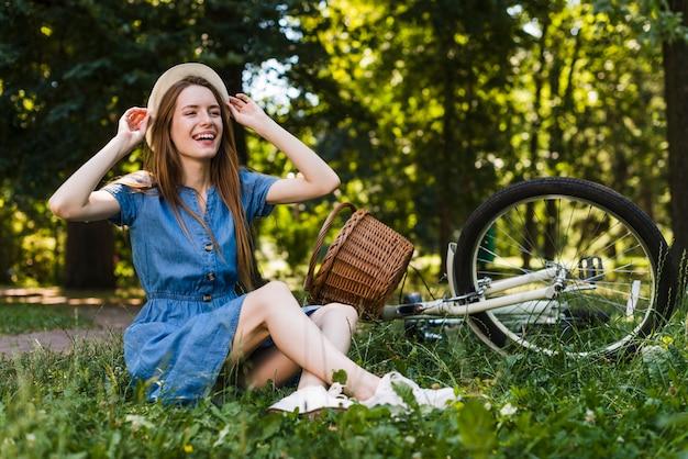 自転車の横にある芝生の上に座っている女性