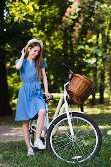 幸せな女が彼女の自転車でポーズ