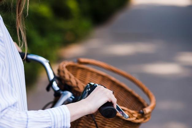 自転車のハンドルを保持している女性のクローズアップ