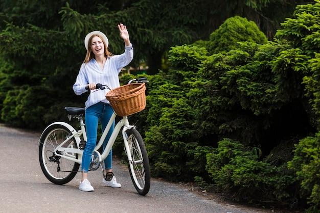 手を振っている自転車を持つ女性