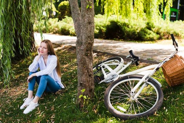 自転車の横にある芝生の上に座る女性