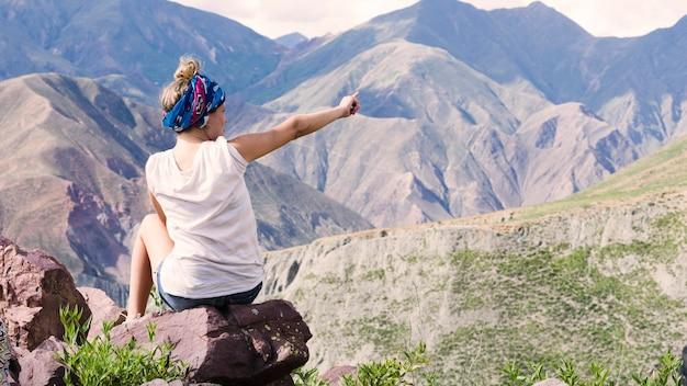 山を指す女性