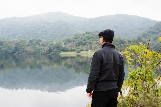 風景を楽しんで湖のそばの男