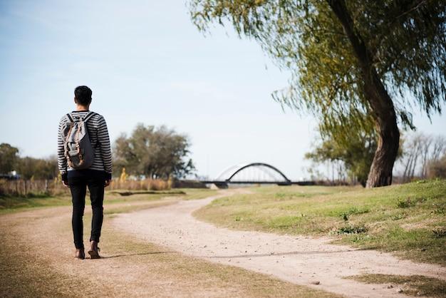 若い男が公園に歩いて