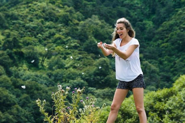 Молодая женщина играет с лепестками цветов на ветру