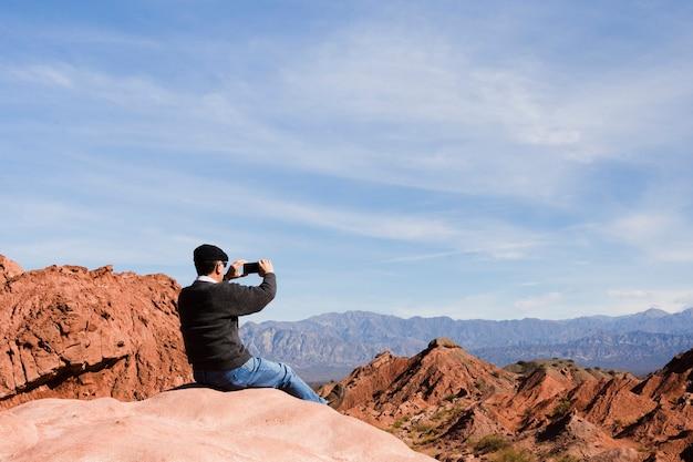 山の風景で写真を撮る男
