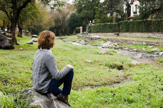川の近くの岩の上に座っている女性