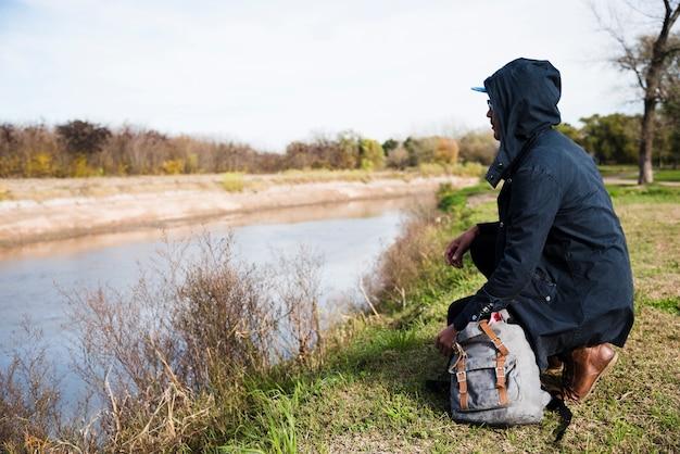 Человек сидит на берегу реки