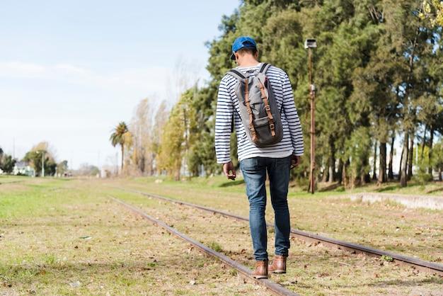 公園のレールの上を歩く若い男