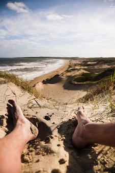 ビーチの風景で足を閉じる