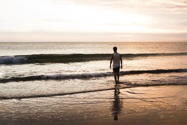Человек купается в океане на рассвете