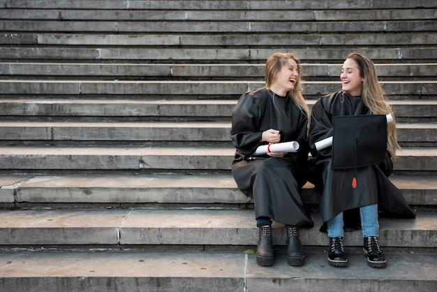 階段で笑っているロングショット大学の友人