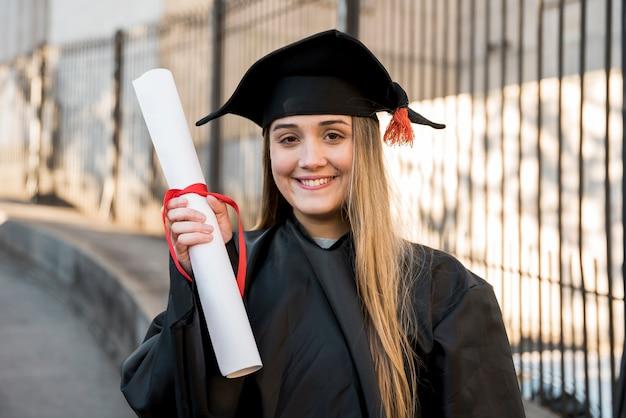 彼女の証明書を保持している大学卒業生